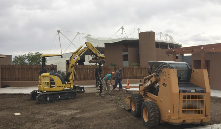"""File - In this May 9, 2017 file photo, Construction workers put final touches on parking lot renovations at the Santa Fe Opera in Santa Fe, N.M. The Santa Fe Opera will hold the world premiere in 2019 of a suspenseful fairy-tale from a Danish composer who created the operatic version of """"The Handmaid's Tale."""" Directors of the Santa Fe Opera on Wednesday, May 9, 2018, announced the new work from Poul Ruders that is inspired by the Brothers Grimm fairy tales. """"The Thirteenth Child"""" is described as a down-to-the wire thriller for audiences of all ages. (AP Photo/Morgan Lee, File)"""