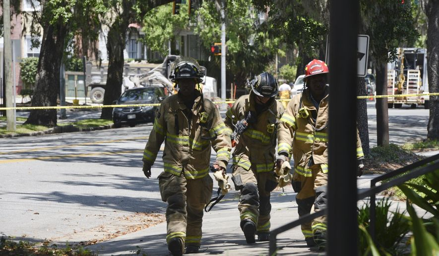 Savannah Fire firefighters walk away from a gas leak on Wednesday, May 9, 2018, in Savannah, Ga. The leak, which began when construction crews hit a gas line, caused the surrounding area to be evacuated. (Will Peebles/Savannah Morning News via AP)