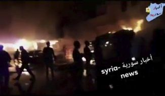 This frame grab from video provided on Wednesday, May, 9, 2018 by Syria News, shows people standing in front of flames rising after an attack on an area known to have numerous Syrian army military bases, in Kisweh, south of Damascus, Syria on Tuesday. The Britain-based Syrian Observatory for Human Rights said the missiles targeted depots and rocket launchers that likely belonged to Iran's elite Revolutionary Guard in Kisweh, killing nine people. (Syria News, via AP)