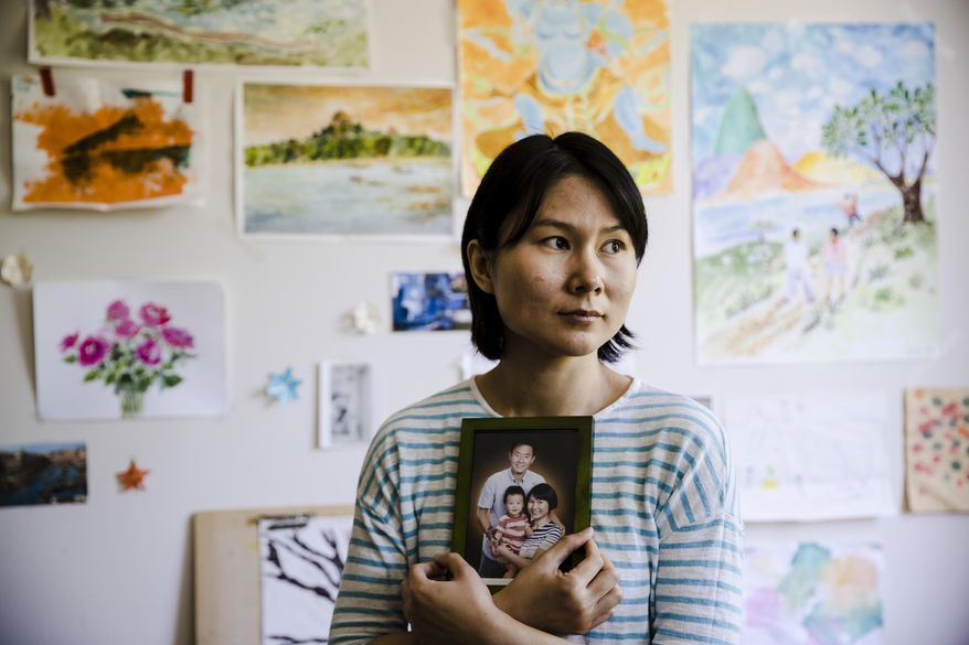 Hua Qu, the wife of Chinese-American Xiyue Wang, poses for a photograph with a portrait of her family in Princeton, N.J., Wednesday, May 9, 2018. Families of several Americans currently detained in Iran are hoping President Donald Trump's decision announced on Tuesday to withdraw from the Iran nuclear deal will not make it harder to get their love ones freed. (AP Photo/Matt Rourke)
