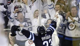 "FILE - In this May 1, 2018, file photo, Winnipeg Jets' Dustin Byfuglien (33) celebrates after scoring against the Nashville Predators during the second period of an NHL hockey playoff game in Winnipeg, Manitoba. The NHL is, indeed, back in ""The 'Peg."" And the Jets are better than ever this year in preparing to play Game 7 of their second-round playoff series at Nashville on Thursday night, May 10. (Trevor Hagan/The Canadian Press via AP, File)"