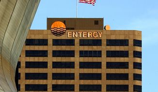 An American waves in the breeze above the Entergy logo in New Orleans. (AP Photo/Bill Haber, file)