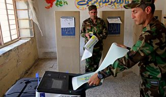 Iraqi soldiers prepare to cast their votes in early voting for Iraq's security forces, prisoners and hospital patients ahead of Saturday's national parliamentary elections, in Baghdad, Iraq, Thursday, May 10, 2018. The vote will be the first since Iraq declared victory over the Islamic State group and the fourth since the 2003 U.S.-led toppling of Saddam Hussein. (AP Photo/Karim Kadim)