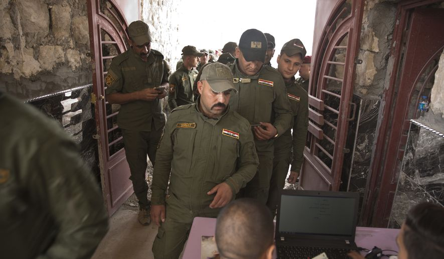 SWAT forces check in with election officials before casting their ballots in early voting for Iraq's security forces, prisoners and hospital patients ahead of Saturday's national parliamentary elections, in Mosul, Iraq, Thursday, May 10, 2018. The vote will be the first since Iraq declared victory over the Islamic State group and the fourth since the 2003 U.S.-led toppling of Saddam Hussein. (AP Photo/Maya Alleruzzo)