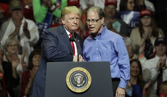 President Donald Trump, left, and Indiana Republican senatorial candidate Mike Braun embrace during a GOP campaign rally Thursday, May 10, 2018, in Elkhart, Ind. (AP Photo/Charles Rex Arbogast)