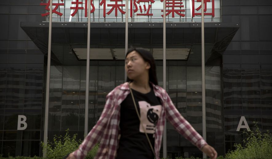 A woman walks past the offices of the Anbang Insurance Group in Beijing, Thursday, May 10, 2018. A court in Shanghai sentenced the founder of the Chinese insurance company that owns New York City's Waldorf Hotel to 18 years in prison on Thursday after he pleaded guilty to fraudulently raising billions of dollars from investors, state media reported. (AP Photo/Mark Schiefelbein)