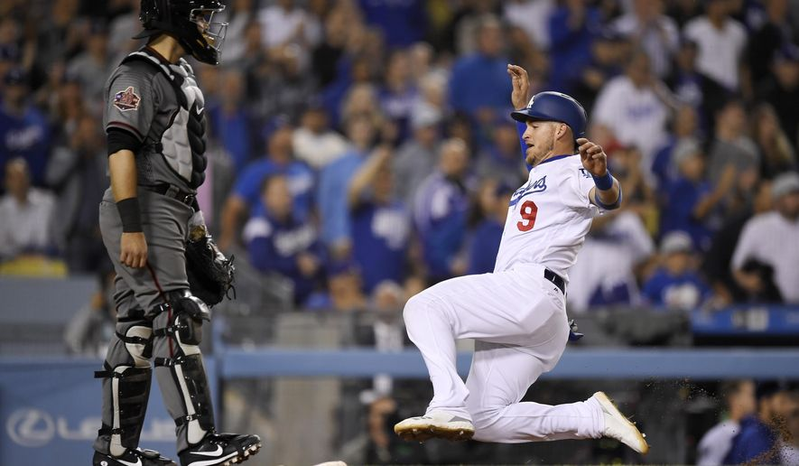 Los Angeles Dodgers' Yasmani Grandal, right, scores on a sacrifice fly by Kyle Farmer as Arizona Diamondbacks catcher Alex Avila stands at the plate during the sixth inning of a baseball game Wednesday, May 9, 2018, in Los Angeles. (AP Photo/Mark J. Terrill)