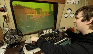 In this Friday, May 4, 2018 photo Tobias Hirsch of the 'Historic City Train Driving Simulator' poses in the simulator cockpit in Berlin, Germany. (AP Photo/Michael Sohn)