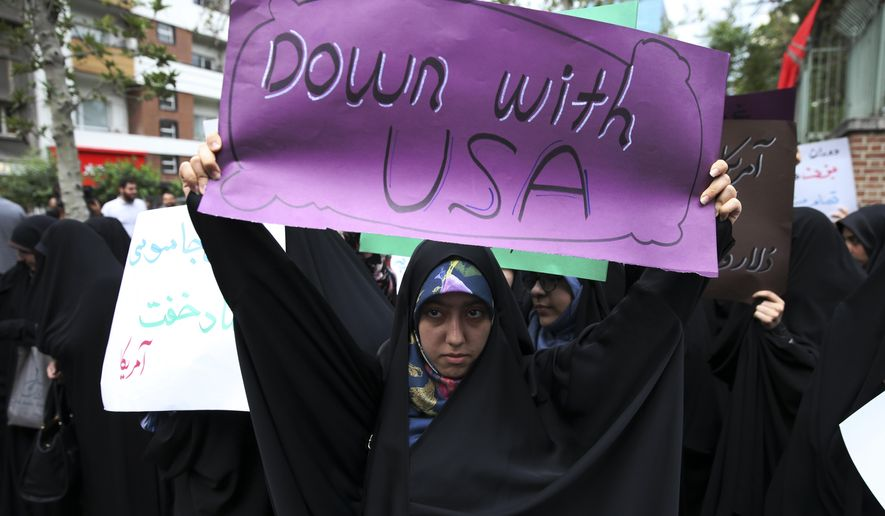 An Iranian demonstrator holds up an anti-U.S. placard during a gathering in front of the former U.S. Embassy in Tehran, Iran, Wednesday, May 9, 2018, reacting to President Donald Trump's decision to pull out of the nuclear deal and renew sanctions on Iran. (AP Photo/Vahid Salemi)