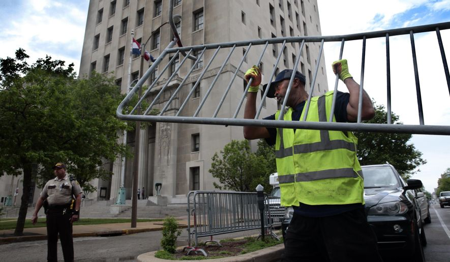 Members of the St. Louis streets department unload barricades on the Chestnut Street side of the Civil Courts building in St. Louis, Mo., on Wednesday, May 9, 2018, in advance of Thursday's start of jury selection in the trial of Missouri Gov. Eric Greitens, who is facing allegations in an invasion-of-privacy case. (Robert Cohen/St. Louis Post-Dispatch via AP)
