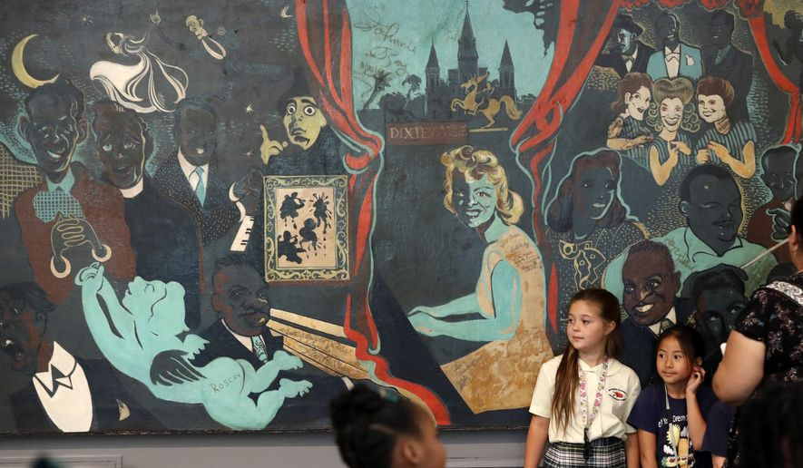 Visitors pose for photos in front of the oil on canvas painting Dixie's Bar of Music at the New Orleans Jazz Museum in New Orleans, Thursday, May 10, 2018. The 29-foot-long painting that caricatures more than 60 musical celebrities of the 1940s is back in a New Orleans museum. The painting covered a wall at Dixie's Bar of Music, a haven for gays during a homophobic era. It's been in storage since 2005's Hurricane Katrina but is now the focus of a new display at the museum in the Old U.S. Mint. (AP Photo/Gerald Herbert)