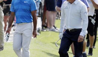 Tiger Woods and Phil Mickelson talk as they walk the 10th fairway during the first round of The Players Championship golf tournament Thursday, May 10, 2018, in Ponte Vedra Beach, Fla. (AP Photo/Lynne Sladky)