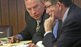 Indianapolis Metropolitan Police Department (IMPD) officer Michal Dinnsen, left, talks with his attorneys during the Civilian Police Merit Board hearing, Thursday, May 10, 2018 in Indianapolis. IMPD officers Carlton Howard and Michal Dinnsen fatally shot unarmed black motorist Aaron Bailey last summer.  (Kelly Wilkinson/The Indianapolis Star via AP)
