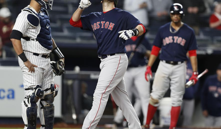 Boston Red Sox right fielder J.D. Martinez points skyward after scoring on his eighth-inning solo home run in a baseball game against the New York Yankees in New York, Thursday, May 10, 2018. Yankees catcher Gary Sanchez is at left. (AP Photo/Kathy Willens)