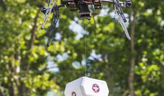 """FILE- In this July 17, 2015, file photo, a Flirtey drone flies above the Wise County Fairgrounds while lowering a package of prescription medication at the Remote Area Medical (RAM) clinic in Wise County, Va. The selection of the Reno-based drone operator Flirtey and its local partners for a national test program aimed at increasing the use of unmanned aircraft will be a """"game-changer"""" for the delivery of emergency medical supplies in the region, backers of the effort say. (Tim C Cox/The Bristol Herald-Courier via AP, File)"""