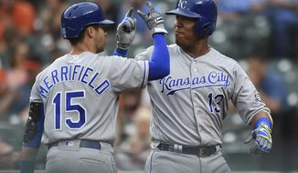Kansas City Royals' Salvador Perez, right, celebrates his grand slam with Whit Merrifield, during the first inning against the Baltimore Orioles in a baseball game Thursday, May 10, 2018, in Baltimore. (AP Photo/Gail Burton)