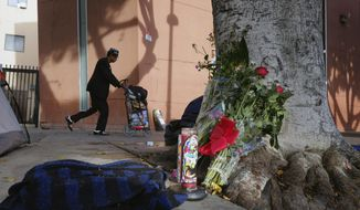 FILE - In this March 2, 2015, file photo, a pedestrian walks past flowers and candles placed on a sidewalk near where Charly Keunang, a homeless man was shot and killed by police in the Skid Row section of downtown Los Angeles. A jury has found the two Los Angeles police officers liable for damages in the fatal 2015 shooting. (AP Photo/Richard Vogel, File)