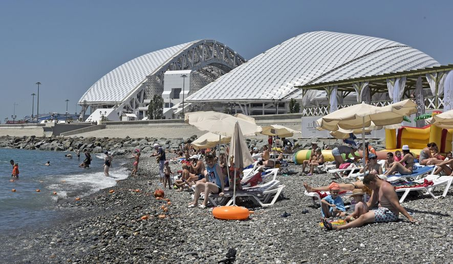 In this photo taken on Monday, June 26, 2017, Russian tourists enjoy the black sea in front of the Fisht stadium in Sochi, Russia. (AP Photo/Martin Meissner)