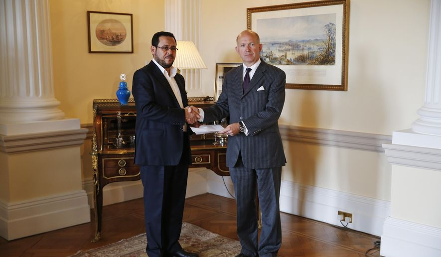 Dominick Chilcott, right, British ambassador in Turkey, poses for photographs with Libyan dissident Abdel Hakim Belhaj, left, during a photo-op at the British Consulate after handing him an apology letter from the UK government, in Istanbul, Thursday, May 10, 2018.  Abdel Hakim Belhaj and his wife, Fatima Boudchar, allege they were detained in southeast Asia in 2004 and sent to Libya to be interrogated by the regime of late dictator Moammar Gadhafi. Britain acknowledged Thursday that its intelligence agents played a role in the kidnapping and torture of an opponent of the late Libyan leader Moammar Gadhafi,  a rare admission of wrongdoing by British spies. (AP Photo/Lefteris Pitarakis)
