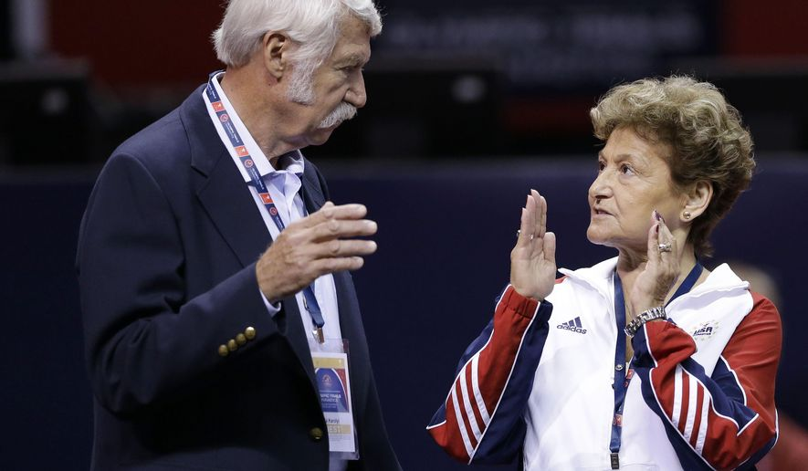 FILE - In this June 29, 2012, file photo, Bela Karolyi, left, and his wife, Martha Karolyi, talk on the arena floor before the start of the preliminary round of the women's Olympic gymnastics trials in San Jose, Calif. Two lawsuits filed this spring against the U.S. Olympic Committee illustrate the peril the USOC finds itself in over its handling of decades' worth of sex-abuse cases, while shining a light on the murky relationship the federation has with the sports organizations it oversees.Martha and Bela Karolyi are suing the USOC, along with USA Gymnastics, seeking damages for the canceled sale of their famed Texas training center _ a transaction that tanked in the wake of sex-abuse cases involving team doctor Larry Nassar. (AP Photo/Gregory Bull, File)