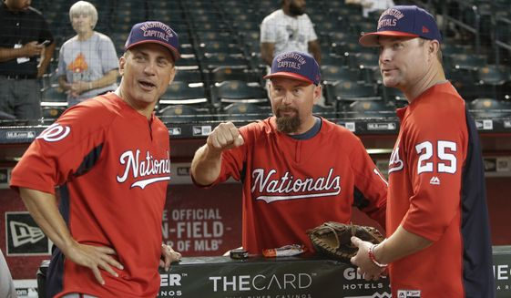 Washington Nationals Tim Bogar (24), Bob Henley (13), and Joe Dillon (25) wear a Washington Capitals hat before a baseball game against the Arizona Diamondbacks, Friday, May 11, 2018, in Phoenix. (AP Photo/Rick Scuteri) ** FILE **
