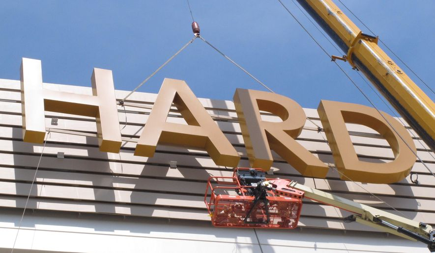 This Friday, May 4, 2018 photo shows part of the first sign for the soon-to-open Hard Rock Casino in Atlantic City N.J., being lifted into place on the building. As Atlantic City's casinos mark their 40th anniversary, the industry is hailing the reopening of two of the five casinos that shut down since 2014, though some worry that re-expanding the market could lead to the same conditions that caused the closings in the first place. Hard Rock, which is the former Trump Taj Majal, and Ocean Resort, which is the former Revel, are both due to open on June 28. (AP Photo/Wayne Parry)