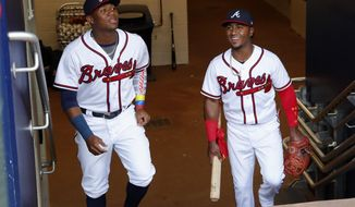 In this Saturday, May 5, 2018 photo, Atlanta Braves left fielder Ronald Acuna Jr., left, and second baseman Ozzie Albies (enter the dugout before a baseball game against the San Francisco Giants in Atlanta. Acuna and Albies are two of the youngest players in major League Baseball. (AP Photo/John Bazemore)
