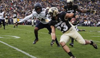 FILE - In this Oct. 28, 2017, file photo, California cornerback Camryn Bynum, back, pursues Colorado running back Phillip Lindsay in the second half of an NCAA college football game in Boulder, Colo. Lindsay is taking part in the Denver Broncos rookie camp. (AP Photo/David Zalubowski, File)