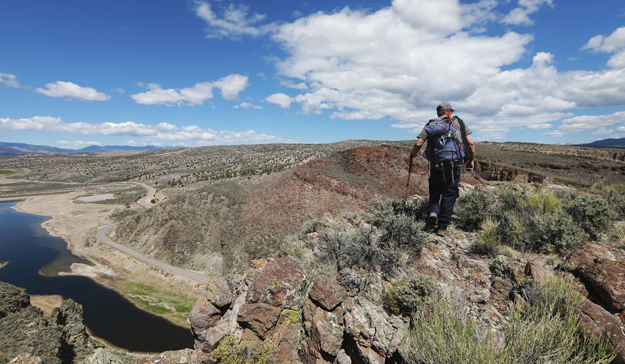 In this Thursday, May 3, 2018 photo, Joe Barnes, a biologist with the Nevada Department of Wildlife, hikes toward a golden eagle nesting site outside of Pioche, Nev. The birds, protected by the Bald and Golden Eagle Protection Act and identified by the Nevada Wildlife Action Plan as a species of conservation priority, are thought to be declining in the western United States. (Andrea Cornejo/Las Vegas Review-Journal via AP)