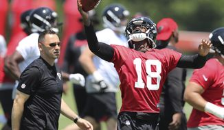 Atlanta Falcons offensive coordinator Steve Sarkisian, left, looks on as first round draft pick wide receiver Calvin Ridley catches a pass at the team's NFL football rookie minicamp, Friday, May 11, 2018, in Flowery Branch, Ga.  (Curtis Compton/Atlanta Journal-Constitution via AP)