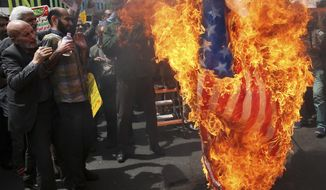 Iranian protestors burn a representation of a U.S. flag during a gathering after their Friday prayer in Tehran, Iran, Friday, May 11, 2018. Thousands of Iranians took to the streets in cities across the country to protest U.S. President Donald Trump's decision to pull out of the nuclear deal with world powers. (AP Photo/Vahid Salemi)