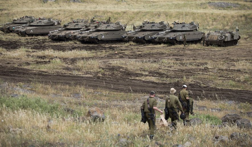 Israeli soldiers walk past tanks in the Israeli-controlled Golan Heights, near the border with Syria, Thursday, May 10, 2018. Israel says it struck dozens of Iranian targets in Syria overnight in response to a rocket barrage on Israeli positions in the Golan Heights. It was the biggest Israeli strike in Syria since the 1973 war. (AP Photo/Ariel Schalit)