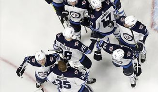 Winnipeg Jets celebrate after defeating the Nashville Predators 5-1 in Game 7 of an NHL hockey second-round playoff series Thursday, May 10, 2018, in Nashville, Tenn. The Jets advanced to the Western Conference final. (AP Photo/Mark Humphrey)