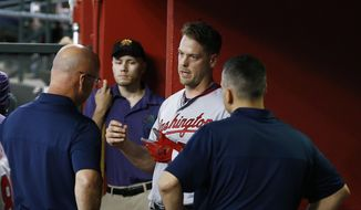 Washington Nationals catcher Matt Wieters, second from right, talks with training staff in the dugout after leaving the baseball game with an injury, during the second inning against the Arizona Diamondbacks on Thursday, May 10, 2018, in Phoenix. (AP Photo/Ross D. Franklin) **FILE**