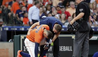 Houston Astros center fielder George Springer (4) is checked after getting hit by a pitch from Texas Rangers' Cole Hamels, as umpire Greg Gibson, right, watches during the third inning of a baseball game Friday, May 11, 2018, in Houston. (AP Photo/Michael Wyke)