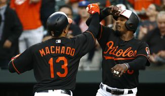 Baltimore Orioles' Manny Machado, left, greets teammate Adam Jones after batting him in on a two-run home run in the first inning of a baseball game against the Tampa Bay Rays, Friday, May 11, 2018, in Baltimore. (AP Photo/Patrick Semansky)