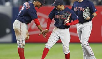 Boston Red Sox shortstop Xander Bogaerts, left, center fielder Mookie Betts, center, and right fielder J.D. Martinez celebrate after the Red Sox defeated the New York Yankees 5-4 in a baseball game in New York, Thursday, May 10, 2018. (AP Photo/Kathy Willens)