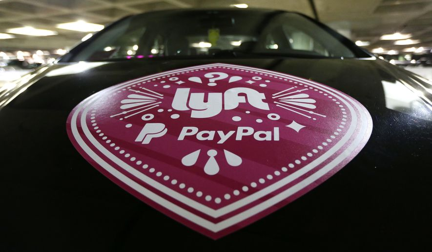 In this March 31, 2016, a Lyft ride-hailing service logo is displayed on a vehicle at Seattle-Tacoma International Airport in Seattle.  (AP Photo/Ted S. Warren, File) **FILE**