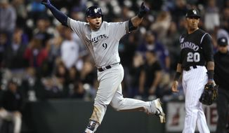 Milwaukee Brewers' Manny Pina celebrates after hitting a two-run home run, next to Colorado Rockies first baseman Ian Desmond during the ninth inning of a baseball game Friday, May 11, 2018, in Denver. (AP Photo/David Zalubowski)