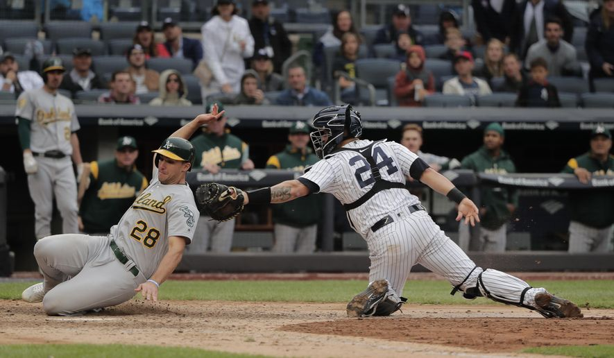 New York Yankees catcher Gary Sanchez (24) tags out Oakland Athletics' Matt Olson (28) at the plate during the ninth inning of a baseball game, Saturday, May 12, 2018, in New York. Olson attempted to score from third on a sacrifice fly by Jonathan Lucroy. (AP Photo/Julie Jacobson)
