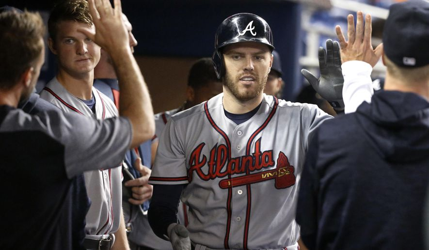 Atlanta Braves' Freddie Freeman, center, is congratulated by teammates after he hit a home run during the first inning of a baseball game against the Miami Marlins, Saturday, May 12, 2018, in Miami. (AP Photo/Wilfredo Lee)