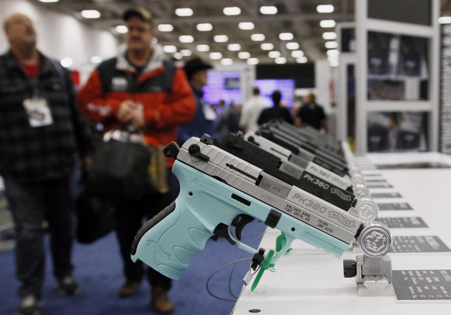 Handguns are on display at the NRA convention in Dallas, Friday, May 4, 2018. Oklahoma's Republican Gov. Mary Fallin vetoed a bill late Friday that would have authorized adults to carry firearms without a permit or training, dealing a rare defeat to the National Rifle Association in a conservative state. (AP Photo/Sue Ogrocki)