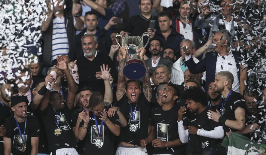 PAOK's players raise the trophy after their 2-0 win against AEK Athens in the Greek Cup soccer final in Athens' Olympic stadium in Athens, Saturday, May 12, 2018. (AP Photo/Yorgos Karahalis)