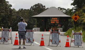 Ken Gadd, a first-time visitor from Dayton, Ohio, takes pictures of the entrance to Volcanoes National Park, Hawaii, Friday, May 11, 2018. The park is closed due to the threat of an explosive volcanic eruption. Warnings that Hawaii's Kilauea volcano could shoot boulders and ash out of its summit crater are prompting people to rethink their plans to visit the Big Island. (AP Photo/Jae C. Hong)