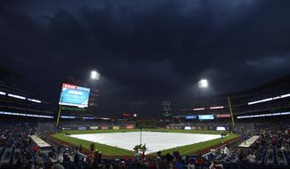 A tarp covers the field prior to a baseball game between the Philadelphia Phillies and the New York Mets as heavy storms were anticipated, Saturday, May 12, 2018, in Philadelphia. (AP Photo/Derik Hamilton)