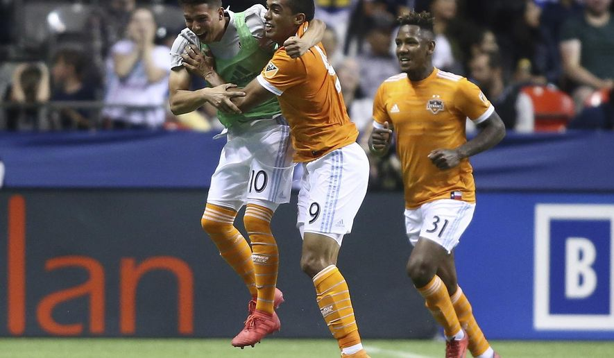 Houston Dynamo forward Mauro Manotas (9) celebrates his goal against the Vancouver Whitecaps with teammates Tomas Martinez (10) and Romell Quioto (31) during the second half of an MLS soccer match Friday, May 11, 2018, in Vancouver, British Columbia. (Ben Nelms/The Canadian Press via AP)