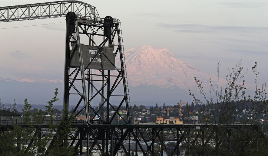 In this May 7, 2018 photo, Mount Rainier is seen at dusk behind the Murray Morgan Bridge in downtown Tacoma, Wash. The eruption of the Kilauea volcano in Hawaii has geologic experts along the West Coast warily eyeing the volcanic peaks in Washington, Oregon and California, including Rainier, that are part of the Pacific Ocean's ring of fire. (AP Photo/Ted S. Warren)