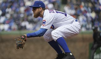 FILE - In this April 10, 2018, file photo, Chicago Cubs first baseman Ben Zobrist plays in place of the injured Anthony Rizzo during the team's baseball game against the Pittsburgh Pirates at Wrigley Field in Chicago. Major League Baseball has warned Zobrist against wearing black cleats. Zobrist posted a letter from the league office on Instagram saying the cleats he wore May 2 against Colorado violated the collective bargaining agreement. MLB says they must be at least 51 percent blue--the Cubs' color--and warned he could be fined and disciplined if he doesn't comply. Zobrist says he has worn black cleats for day games at Wrigley Field the past two years to honor the game's past. (John Starks/Daily Herald via AP)