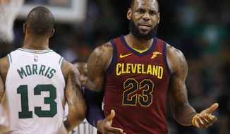 Cleveland Cavaliers forward LeBron James (23) reacts next to Boston Celtics forward Marcus Morris (13) during the third quarter of Game 1 of the NBA basketball Eastern Conference Finals, Sunday, May 13, 2018, in Boston. (AP Photo/Michael Dwyer)