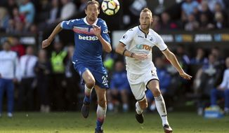 Stoke City's Peter Crouch, left and Swansea City's Mike van der Hoorn battle for the ball, during the English Premier League soccer match between Swansea City and Stoke City,  at the Liberty Stadium, in Swansea, Wales, Sunday May 13, 2018. (David Davies/PA via AP)